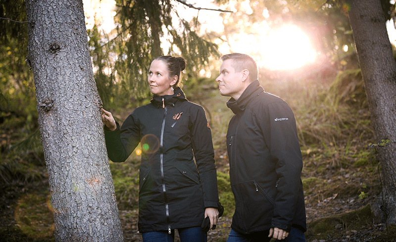 Sanna and Jani examining the condition of a tree on the field