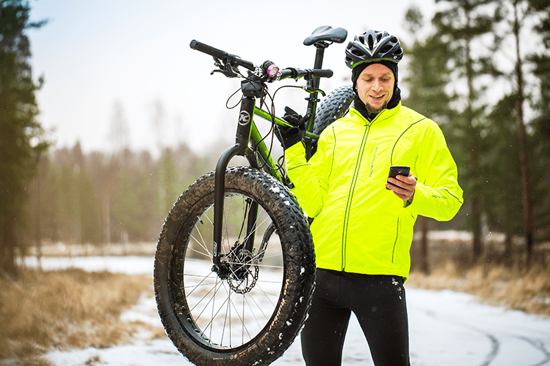 Jussi looking at his phone and carrying his bike outdoors