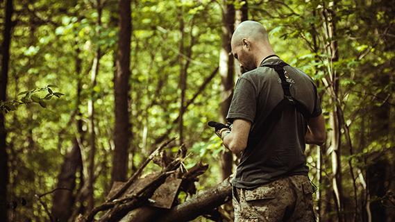 Mies tutkii puhelinta metsässä